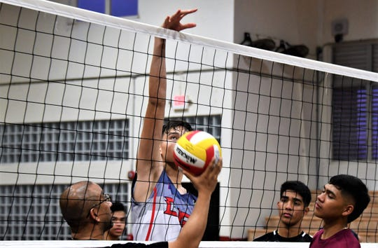 6-foot-8 junior Matthew Fegurgur measures his reach on the 8-foot net during Father Duenas Friars' volleyball practice at the Jungle on March 28. FD coach Steve Pangelinan, left, says it will be a spectacle to behold when Fegurgur figures out volleyball's intricate timings.