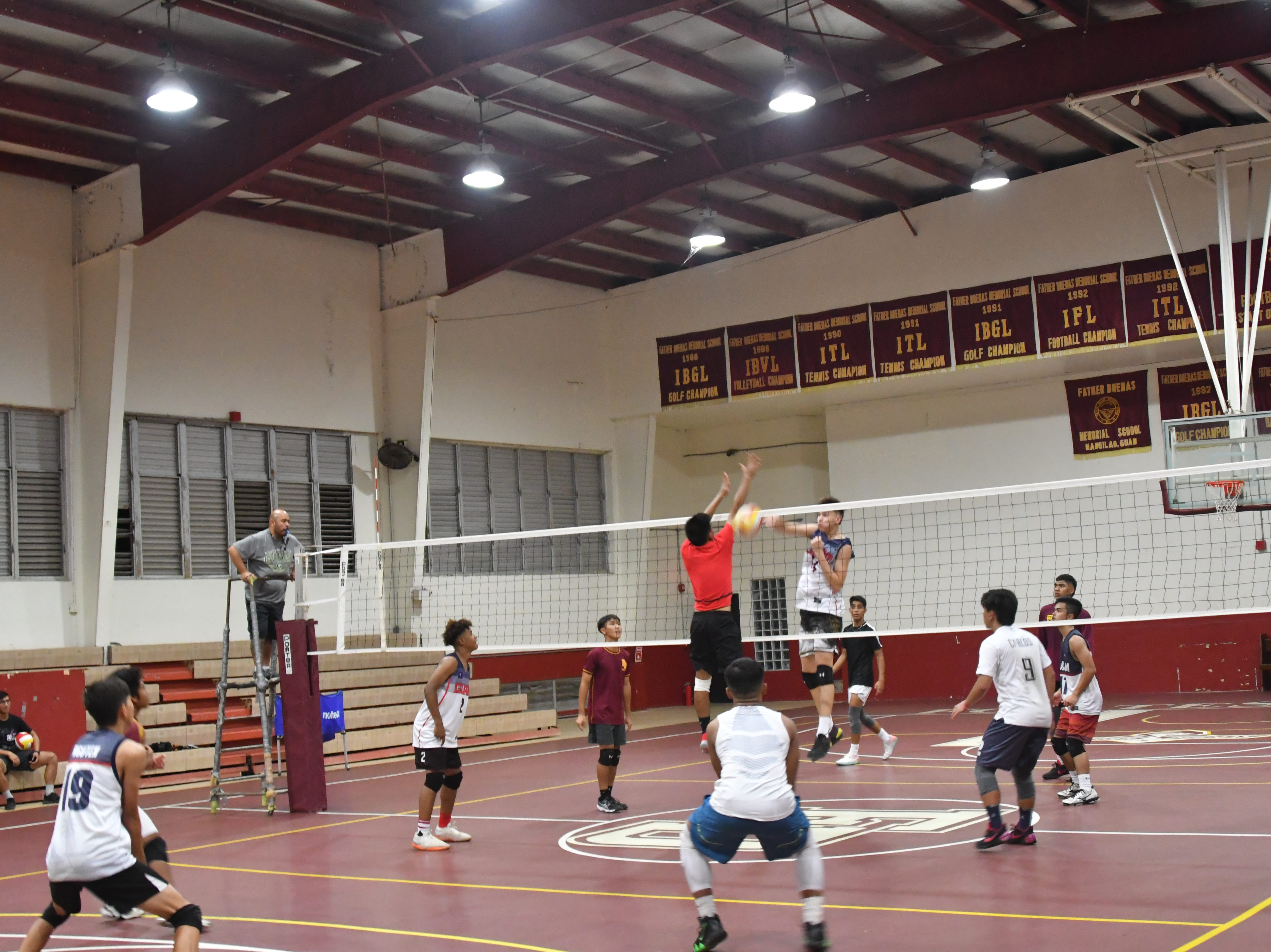 Matthew Fegurgur, center, on far court, spikes a quick set past Rich Salas during practice at Father Duenas on March 28.