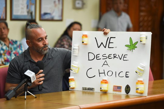 John Concepcion, a military veteran and pro-recreational cannabis supporter, displays a sign with bottles of his medication during a meeting at the Ricardo J. Bordallo Governor's Complex in Adelup, March 29, 2019.