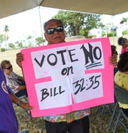 Albert Santos holds a sign in opposition of Bill 32 during a protest at the Ricardo J. Bordallo Governor's Complex in Adelup, March 29, 2019.