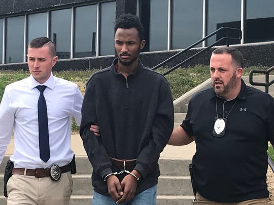 Mohamud Abdikadir, 21, is escorted from the Henderson Police Department by, at left, Detective Jake Isonhood and, right, Detective Eric Ramsey. He has been lodged in the Henderson County Detention Center.