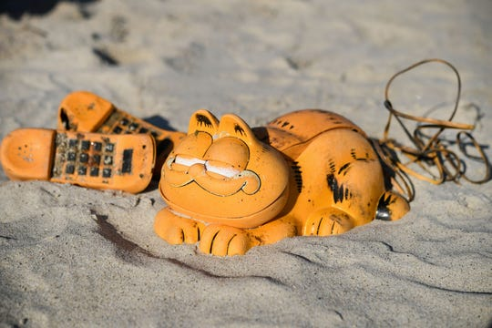 Spare parts of plastic 'Garfield' phones are displayed on the beach on March 28, 2019 in Plouarzel, western France, after being collected from a sea cave by environmental activists. For more than 30 years, plastic phones in the shape of the famous cat 'Garfield' have been washing up on French beaches. The mystery is now solved: a shipping container, which washed up during a storm in the 1980s, was found in a hidden sea cave.