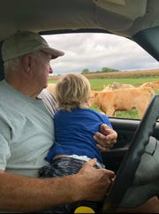 """Forest """"Hink"""" Albertson and his great- grandson Cooper visit the pregnant cows before one gave birth to Victor OlaBeefo."""