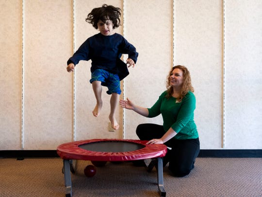 Heather Hantz's son Harrison, 6, a Tennessee boy with autism, jumps on a trampoline with physical therapist Dawn Morgan. Harrison is one of at least 128,000 Tennessee children who lost insurance coverage for therapies like this due to mass enrollment from TennCare and CoverKids.
