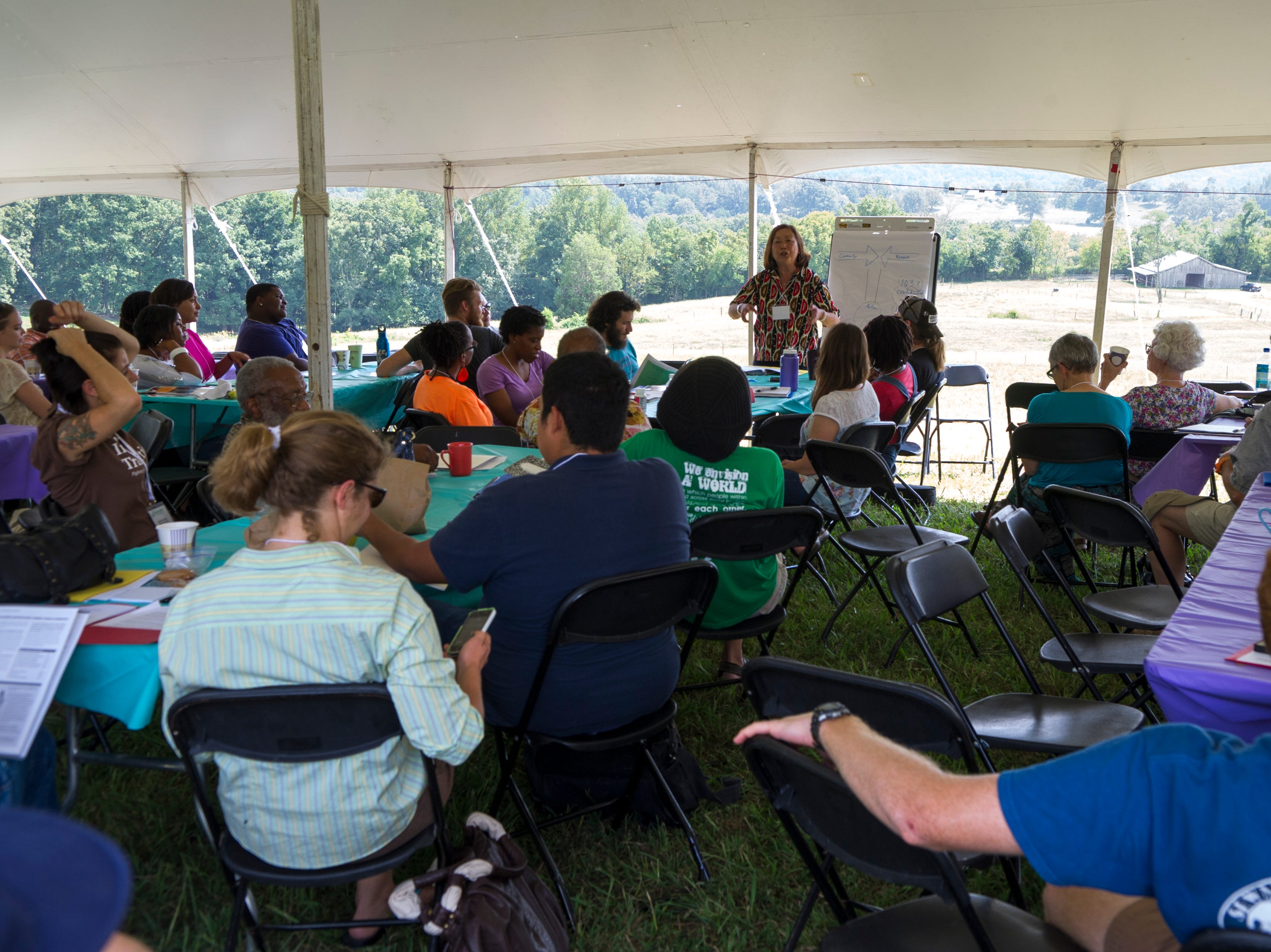 Pam Tau Lee, standing background, leads a participatory action research workshop during the 80th anniversary celebration at the Highlander Research and Education Center in New Market Saturday, Sept. 1, 2012.