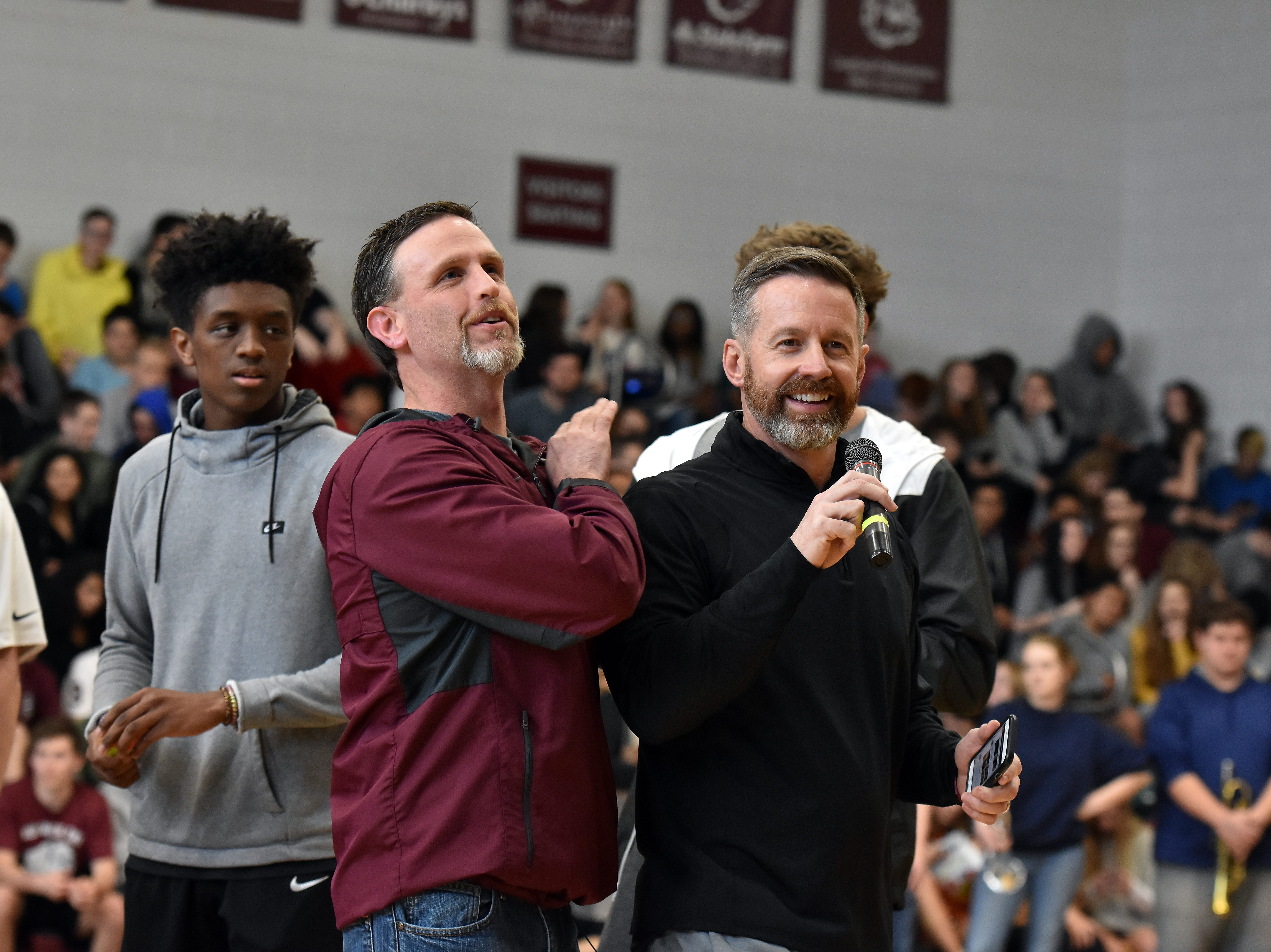 Bearden athletic director Donald Balcom congratulates basketball coach Jeremy Parrott during the pep rally honoring the state championship team on Friday, March 29.