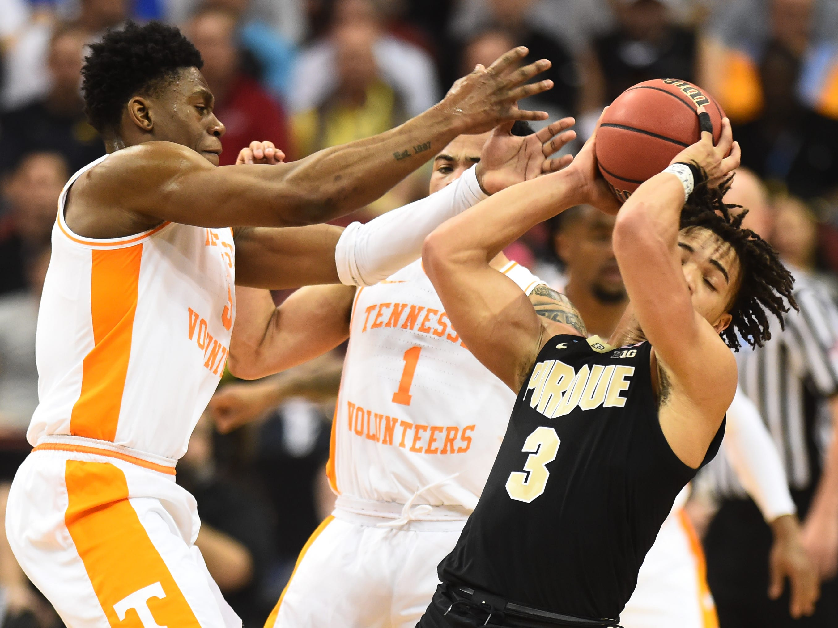 Tennessee guard Admiral Schofield (5) and guard Lamonte Turner (1) defend against Purdue guard Carsen Edwards (3) during the first half of the Sweet 16 game in the NCAA Tournament Thursday, March 28, 2019, at the KFC Yum! Center in Louisville, Ky.