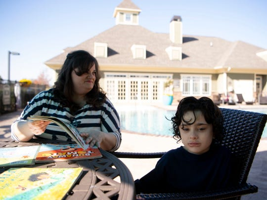 """Heather Hantz reads to her son Harrison, 6, who has autism, at their home in Cleveland, Tennessee. The state government revoked Harrison's TennCare insurance last year, which Hantz said was """"catastrophic"""" to Harrison's autism treatment."""