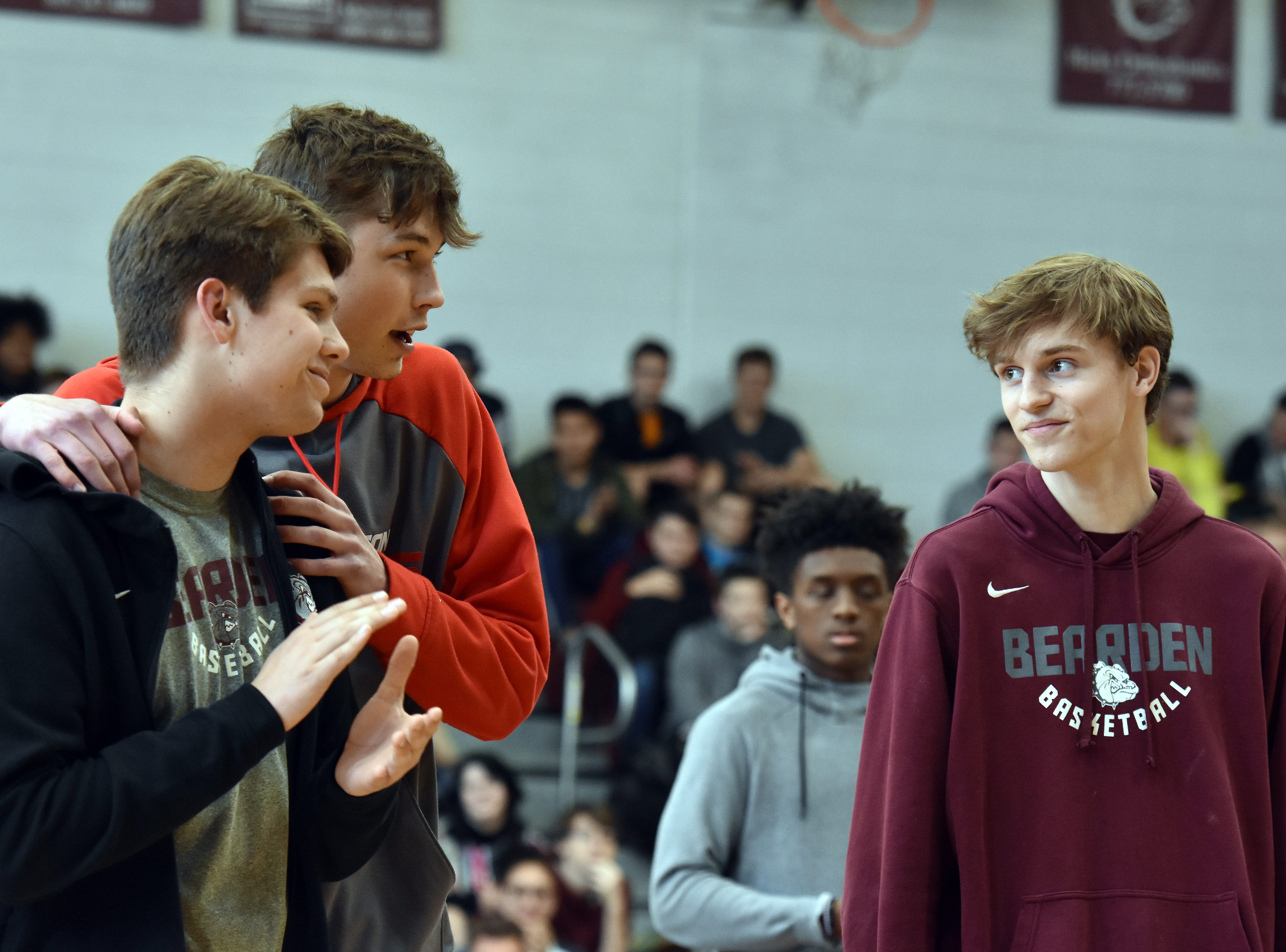 Drew Pember, second from left, hugs a teammate during the pep rally to celebrate the basketball team bringing home the state championship.