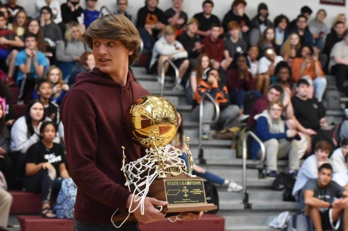 Bearden High basketball player Kordell Kah carries the state championship trophy into the gym as the school celebrates the team during a pep rally on Friday, March 29.