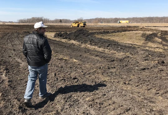As crews from Milestone Contractors work in the background, Eric Erskin walks the freshly graded dirt of the 20 acres of what will become Abby & Libby Memorial Park, near the corner of the Hoosier Heartland Highway and Indiana 218, a mile north of Delphi, on Wednesday, March 27, 2019. The park will be a memorial to Abby Williams and Libby German, two Delphi eighth-graders murdered while hiking a popular community trail near Delphi on Feb. 13, 2017. Erskin is Williams' grandpa.