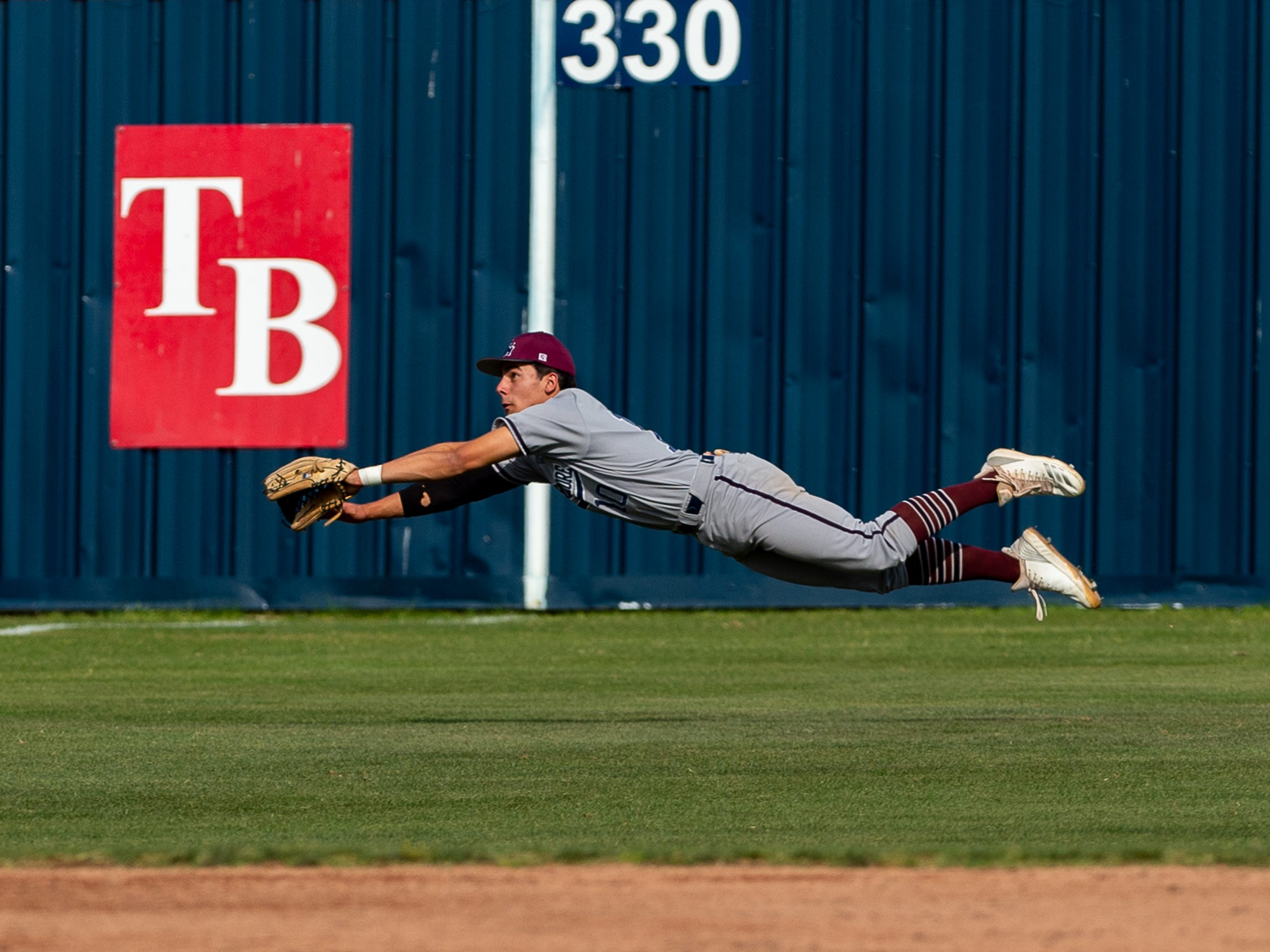 Jake LaPrarie dives for a ball in left field as Teurlings Catholic host St Thomas More baseball. Thursday, March 28, 2019.
