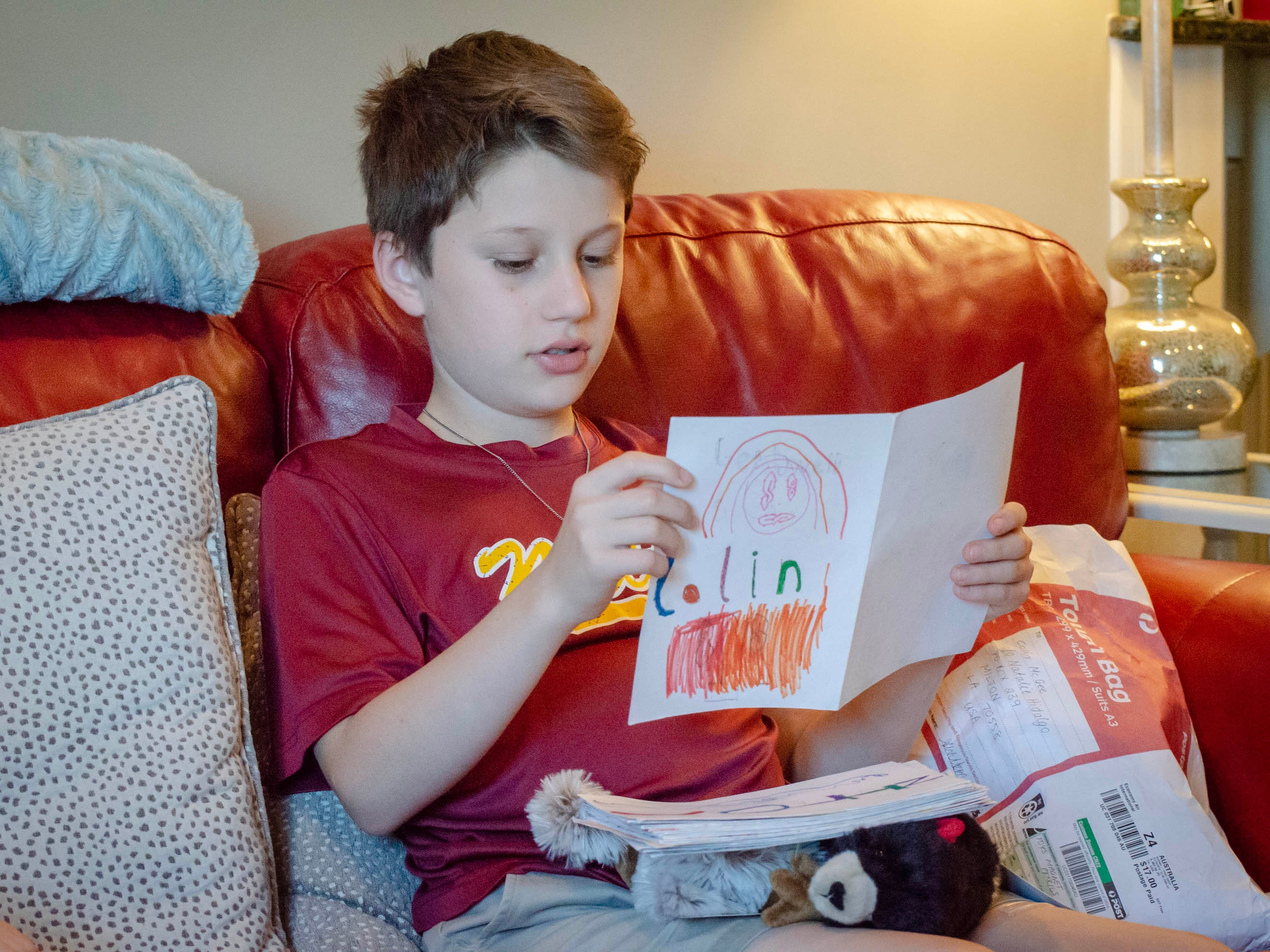 Colin McGee reads and shows letters sent to him from Australia. Colin, 11, had a 7-inch malignant tumor and kidney removed, went through months of chemotherapy. He rang the bell celebrating his remission in January.