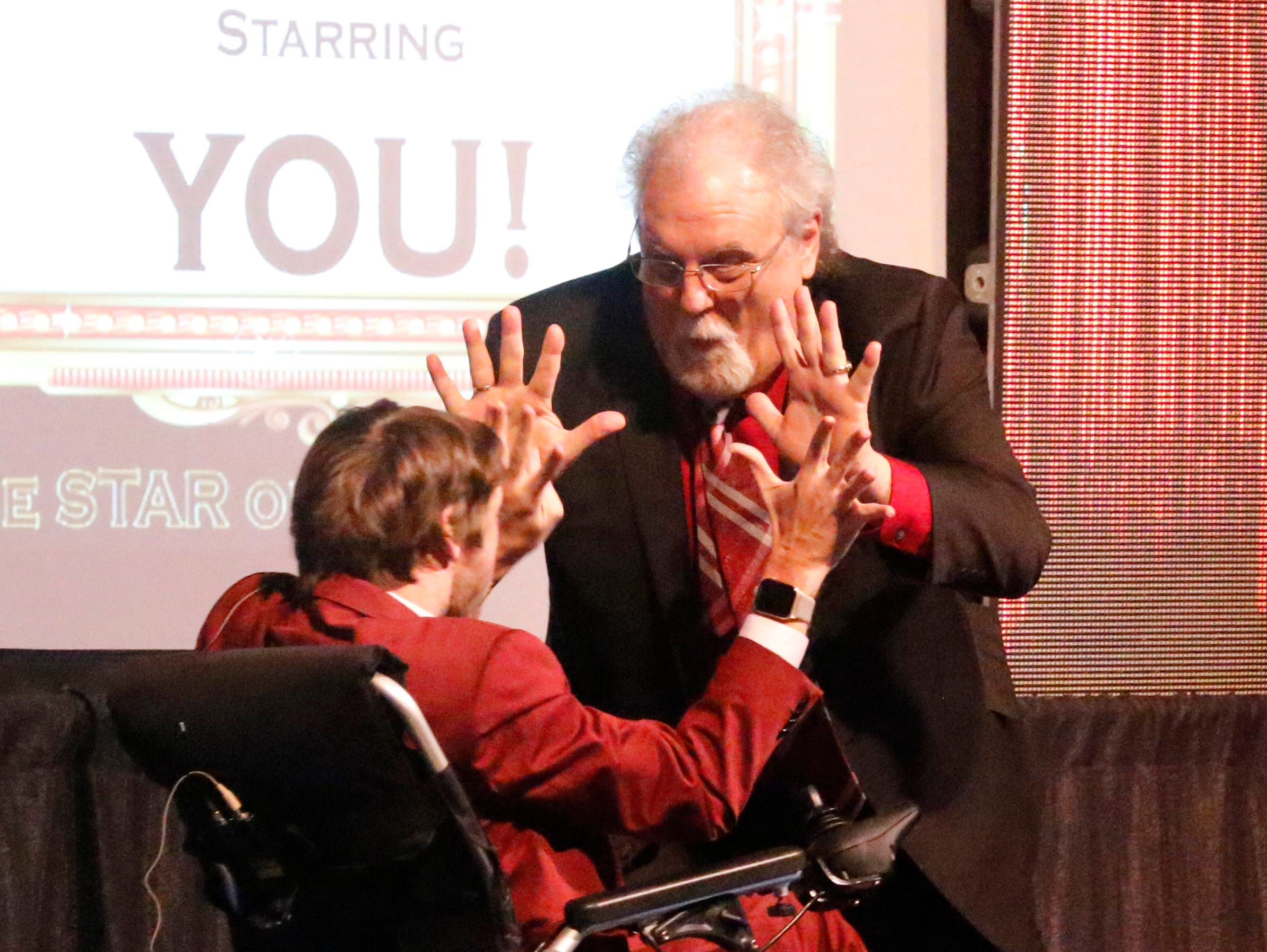 Fairfield County Board of Developmental Disabilities Superintendent John Pekar high fives Zach Anner as they co-host the Fairfield County Board of Developmental Disabilities Celebration of Possibilities Thursday night, March 28, 2019, in Lancaster.