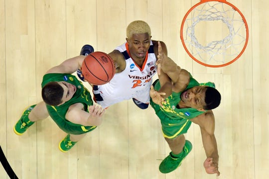 Virginia's Mamadi Diakite (25) puts up a shot against Oregon's Payton Pritchard, left, and Francis Okoro (33) during the Sweet 16 at the KFC Yum Center.
