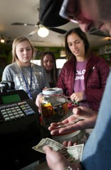 From l. Katie Rutledge of Linden, Melanie Storm of Fenton, and Chloe Rey of East Lansing cash out with Golden Harvest maitre d' Brandon Blanchard Friday morning, March 29, 2019, at the diner in Old Town. The diner has been cash-only since opening in 1952.