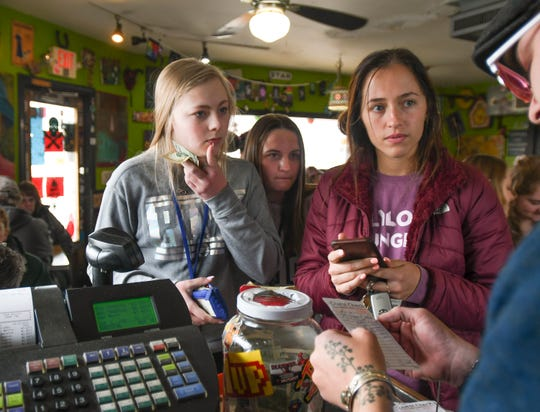 From l. Katie Rutledge of Linden, Melanie Storm of Fenton, and Chloe Rey of East Lansing have their checks split up by maitre d' Brandon Blanchard Friday morning, March 29, 2019, at the Golden Harvest in Lansing's Old Town. The diner has been cash-only since opening in 1952.