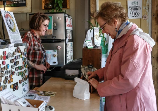 Karen Bircher from St. Johns buys some chocolates from Megen Hurst, co-owner of Oh Mi Organics with cash Thursday, March 28, 2019. Oh Mi Organics is one of the few cash only businesses in the area.