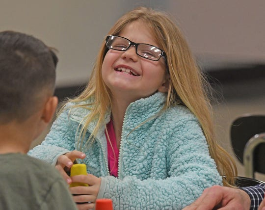 First-grader Kate Trumpower enjoys board games Friday afternoon at Lucas Elementary School during March DADness event.