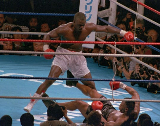 Buster Douglas stands over Mike Tyson after knocking him down, and out, in the 10th round of their Feb. 11, 1990 fight to become undisputed heavyweight champion of the world.