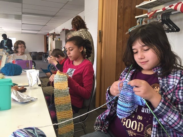 Lilly Melton, 11, at left, and Nadine Cruz, 10,  are part of the Thursday afternoon Police Athletic League or PAL Knitters group held at at Friendly House's after-school program.