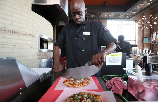 Kitchen pizza lead George Harris slices up some pies at the Malco Powerhouse Cinema Grill & Bar on Thursday, March 28, 2019.