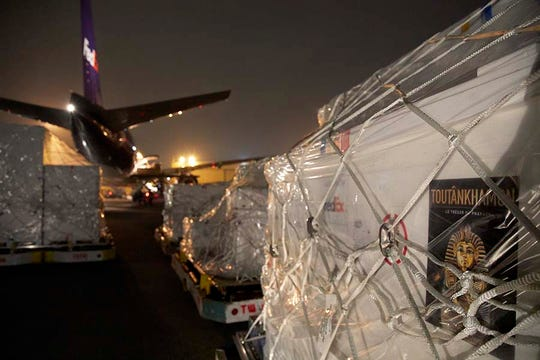 Ancient artifacts in a King Tut exhibit that FedEx Express and FedEx Custom Critical helped transport sit behind a FedEx plane awaiting their next stop.