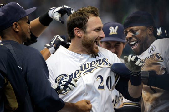 Milwaukee Brewers catcher Jonathan Lucroy is swarmed by  teammates after hitting the game-winning run during the 10th inning against the Colorado Rockies in the regular-season opener Monday, April 1, 2013 at Miller Park in Milwaukee, Wis.