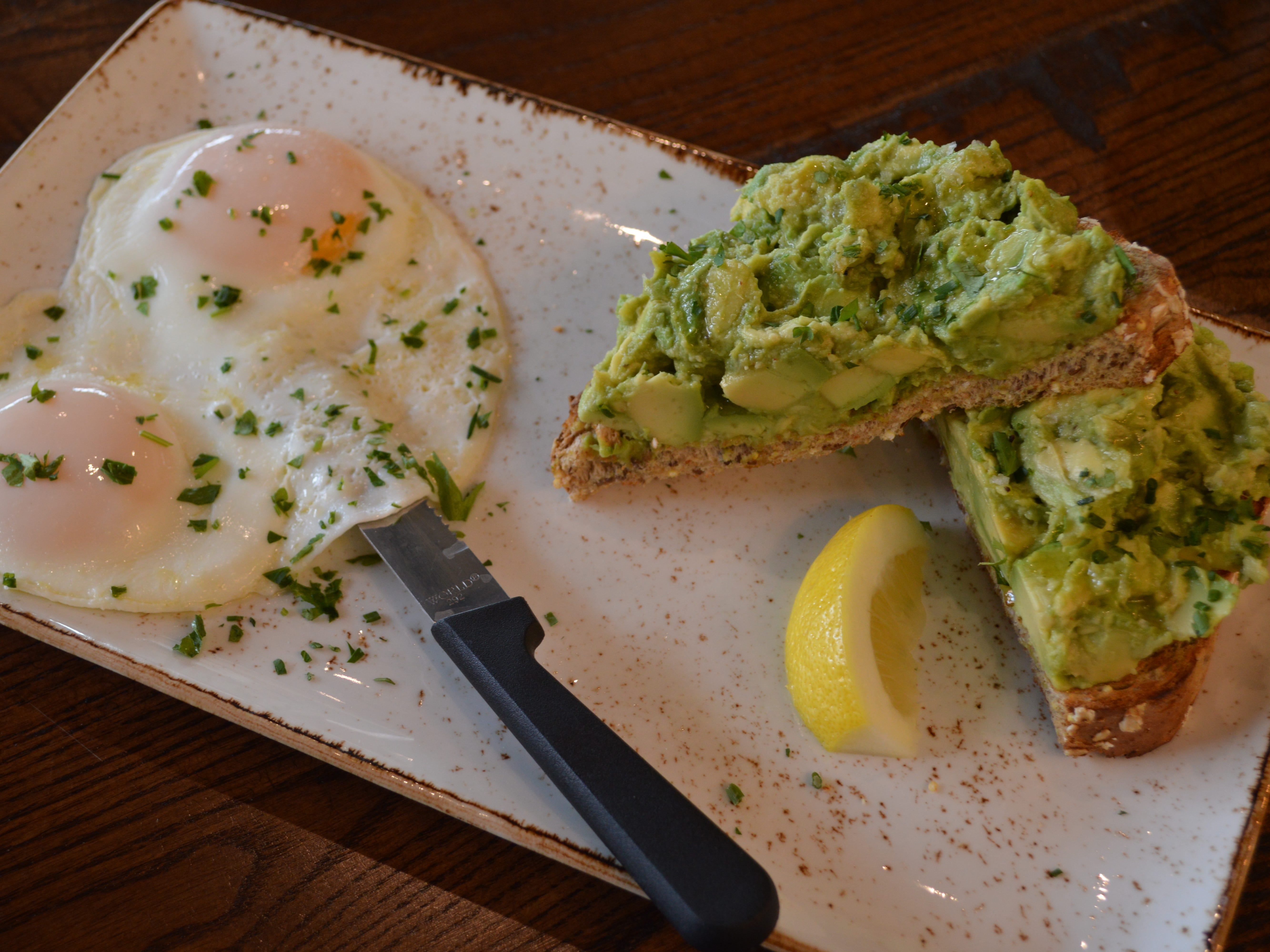 Avocado toast is served with two basted eggs for $10.29.