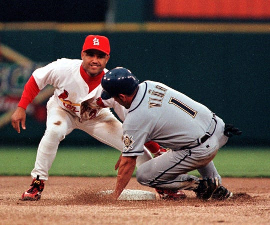 St. Louis Cardinals second baseman Placido Polanco is all smiles as he makes the tag on the Milwaukee Brewers' Fernando Vina (1) during the first inning of the Cardinals' season opener at Busch Stadium in St. Louis Monday, April 5, 1999. Vina was caught attempting to steal second base.