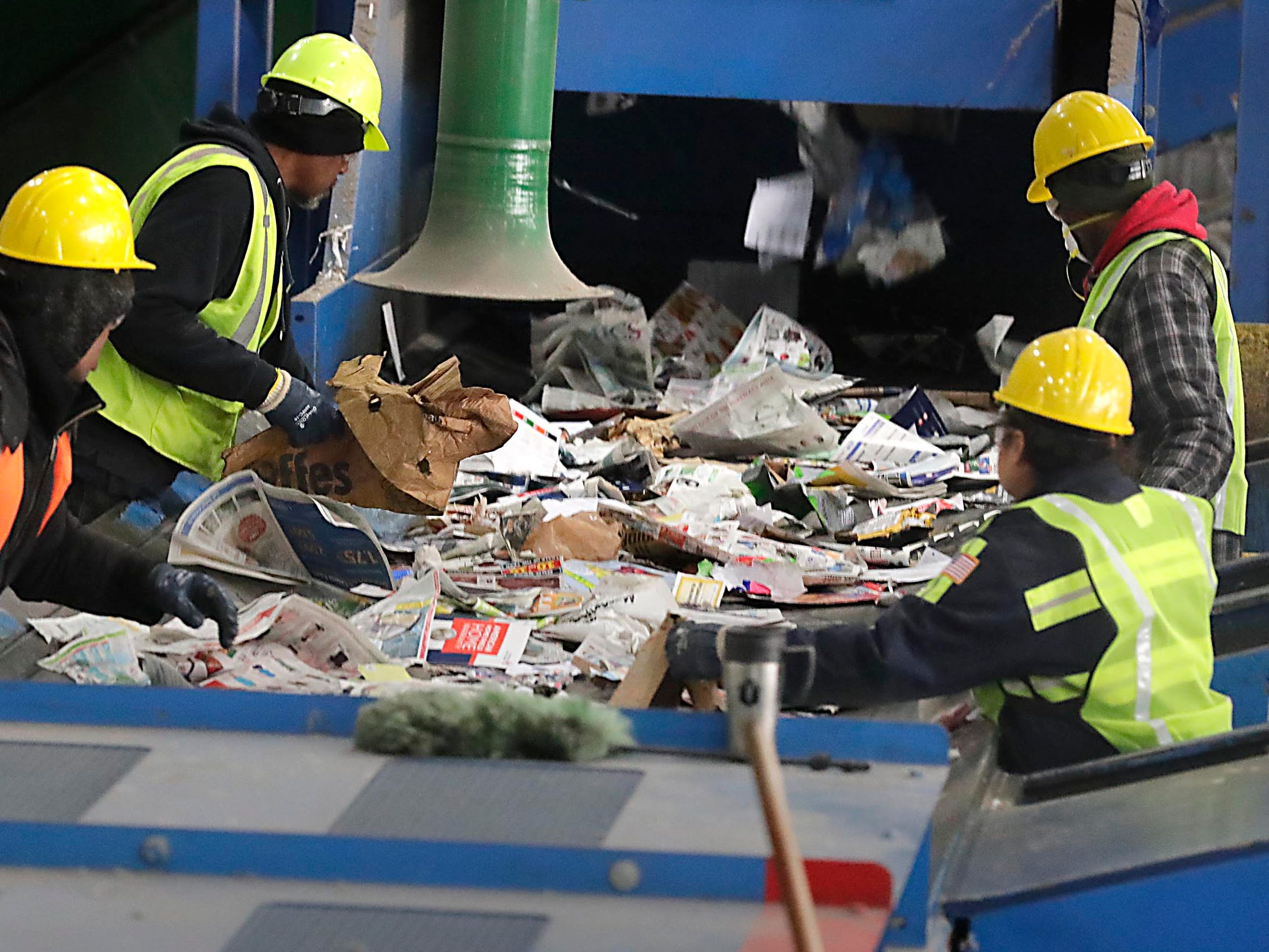 Workers quickly sort and remove items that cannot be recycled from a fast-moving belt at the recycling center in the Menomonee Valley that is jointly owned by the City of Milwaukee and 27 Waukesha County municipalities. Much of their work is removing items people are not supposed to put into their recycling bins, mainly plastic bags that contain other items.