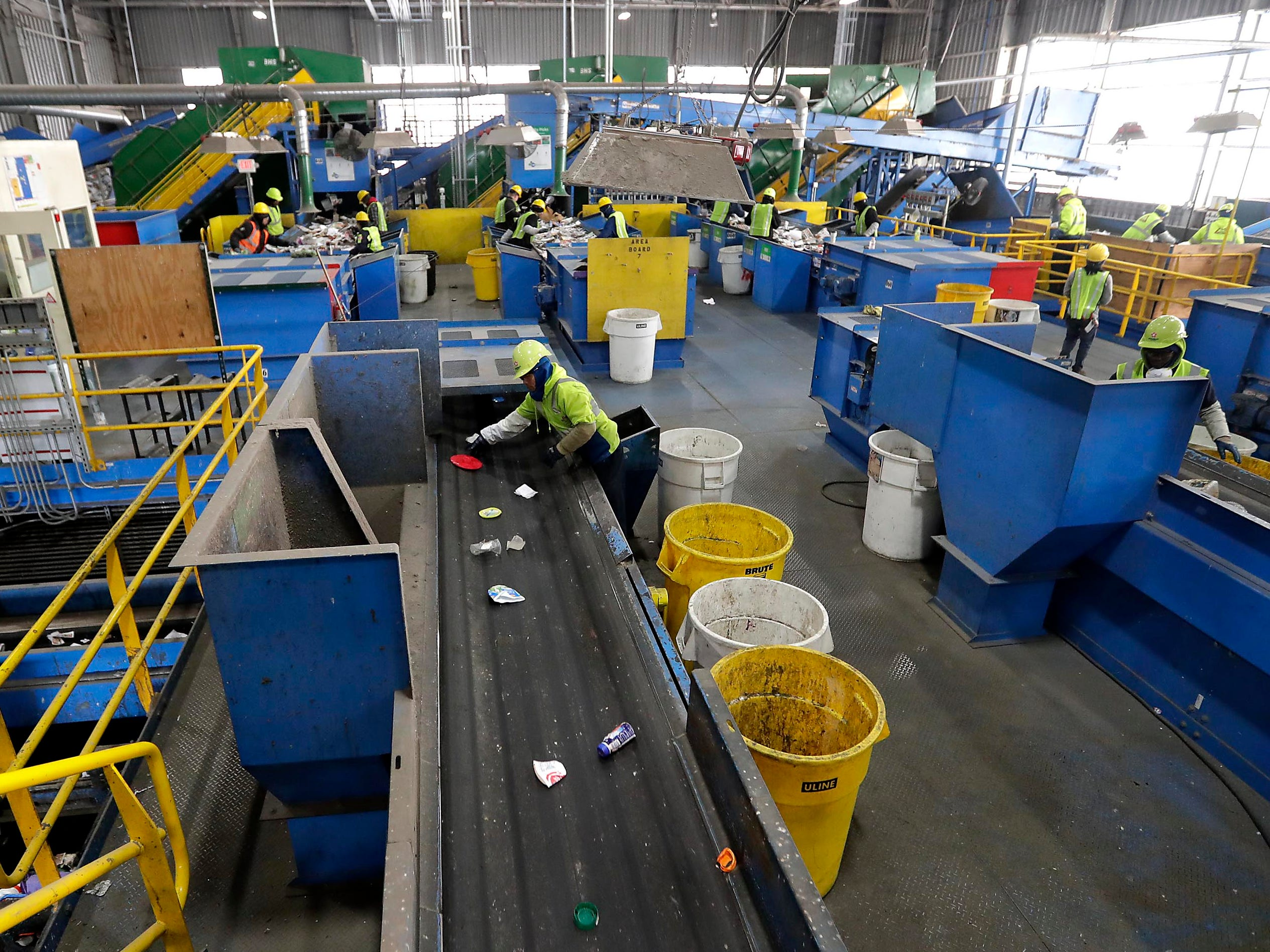 Workers carefully sort items on a conveyor for recycling.