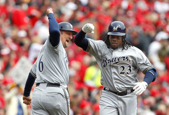 Milwaukee Brewers third base coach Ed Sedar (6) congratulates Rickie Weeks (23) after hitting a home run during the first inning of their opening day MLB National League baseball game against the Cincinnati Reds in Cincinnati, Ohio March 31, 2011.