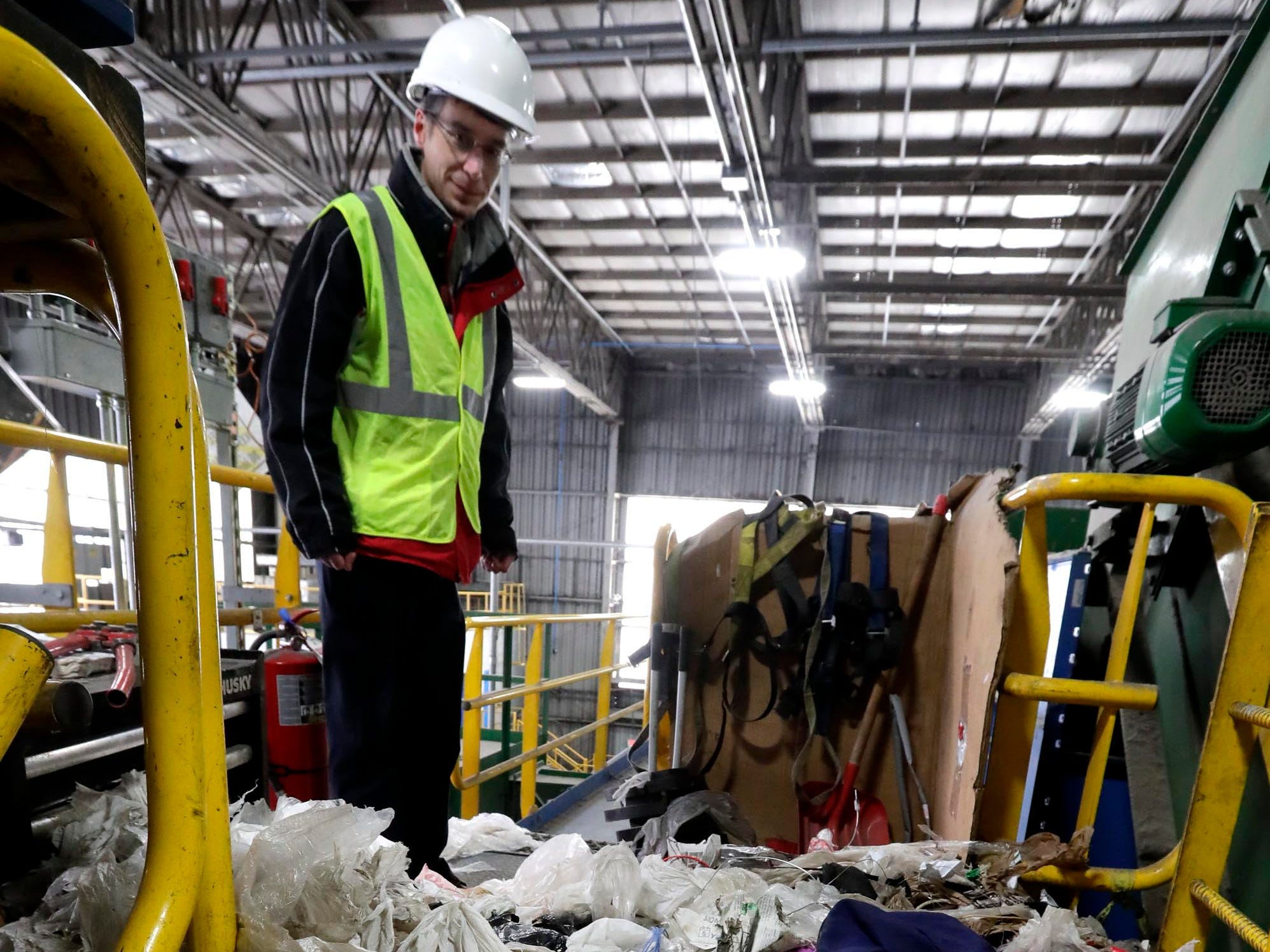 Rick Meyers, sanitation services manager at the recycling center jointly owned by the City of Milwaukee and 27 communities in Waukesha County, shows the plastic bags that were cut from the sorting machines. A conveyor lifts paper products onto spinning disks that sort and compact. Residents often put plastic bags into their recycling bins, which binds up the disks and have to be cut away manually, taking much time away from the sorting process. Recyclable items should be placed loosely in bins, not bagged.