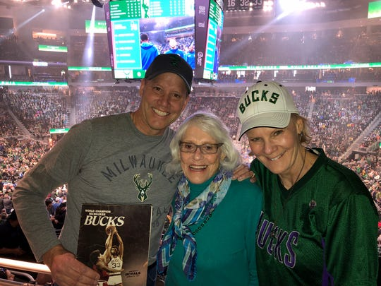 Chuck and Wendy Olsen celebrate their mom, Eugenie, and her 87th birthday at a recent Milwaukee Bucks game. Chuck is holding a game program from the 1971 championship series, when Eugenie took him to Game 3 against the Baltimore Bullets.