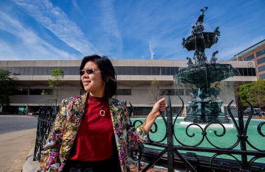 Chintia Kirana is shown in front of the One Dexter Plaza building and the Court Square Fountain in Montgomery, Ala., on Friday March 29, 2019. The Inside Out art project will cover the building with portraits of locals.