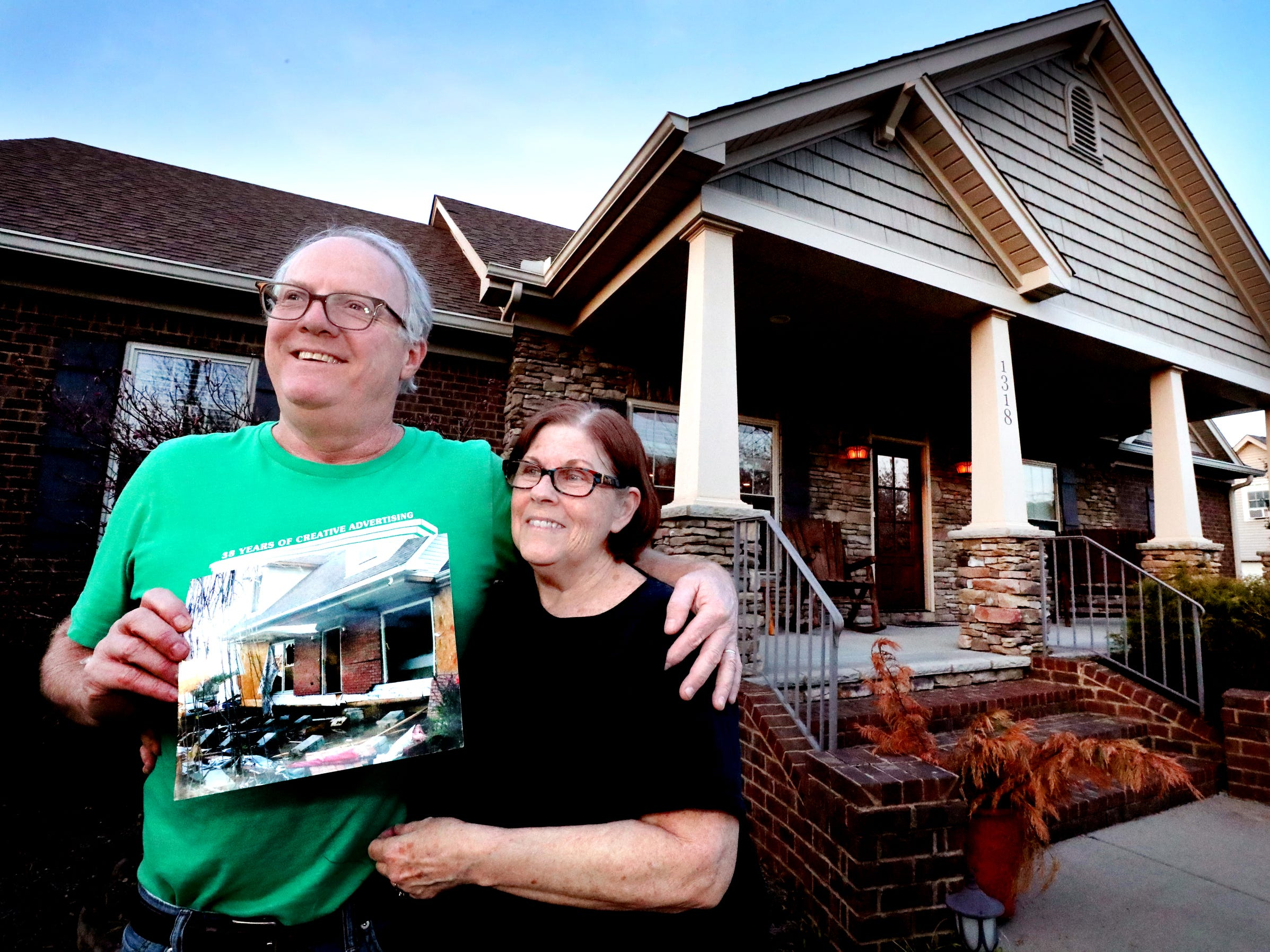 Mike and Teresa Bickford hold up a photo of their old home that was destroyed by the 2009 Good Friday tornado as they stand in front of their new home built on the old site, on Wednesday March 27, 2019.