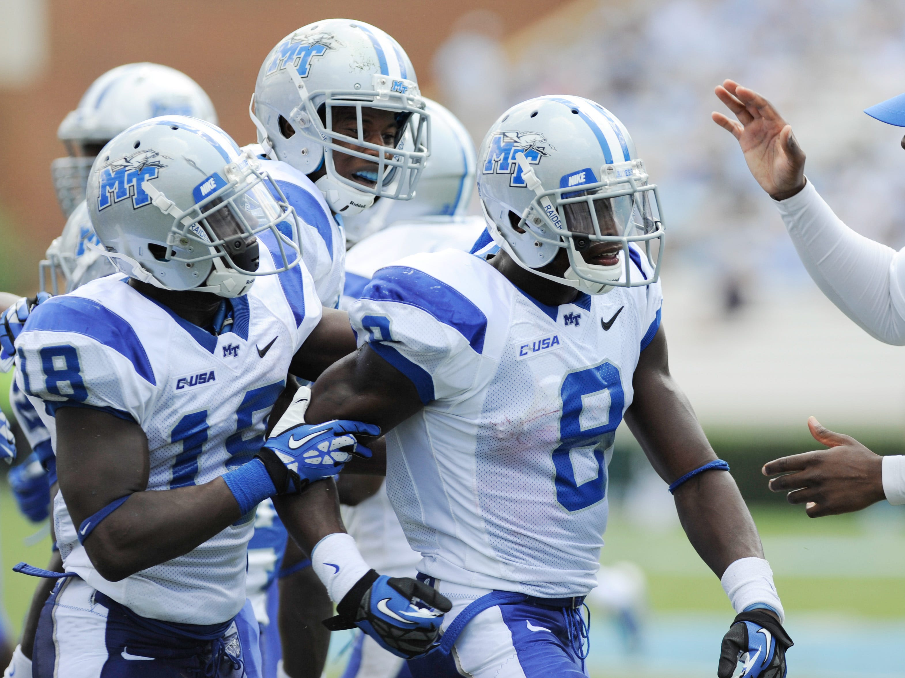 MTSU defensive backs Kenneth Gilstrap (18) and Sammy Seamster (8) are greeted by defensive line graduate assistant Dwight Smith during the Blue Raiders' game against North Carolina in 2013.
