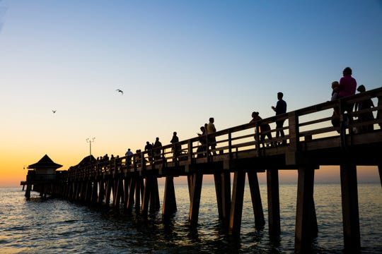 People watch the sunset at the Naples Pier on Wednesday, Dec. 6, 2017.