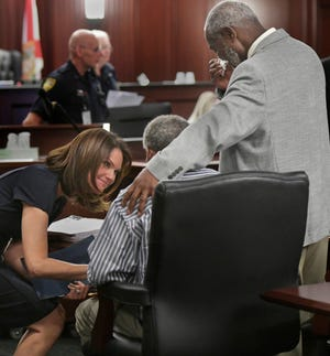 Florida state Attorney Melissa Nelson, left, talks with Clifford Williams, seated, and his nephew, Nathan Myers, after their 1976 murder convictions were overturned in March 2019. They won their freedom as a result of a conviction integrity review unit set up by Nelson. Maricopa County Attorney's Office is establishing a similar unit.