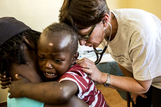 Dr. Tracee Laing, founder and director of Healing Art Missions, checks a baby?s heart rate at the Centre de Sante Clinic in Dumay, Haiti. Laing began HAM in 1998 to satisfy the need for a more permanent clinic.