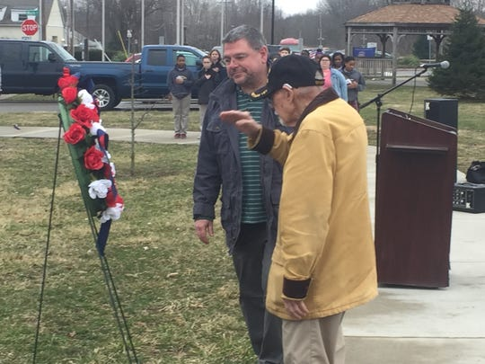 After placing a wreath honoring Vietnam veterans on a stand, Vietnam veteran Harold Cheney Jr. salutes as Harold Cheney III looks on.