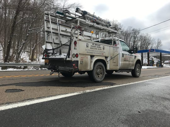 A work truck rumbles on March 1, 2019 over a patchwork Greenwood Lake Turnpike in Ringwood, N.J., where a high-friction road treatment has failed due to the poor condition of the underlying road, state officials said.