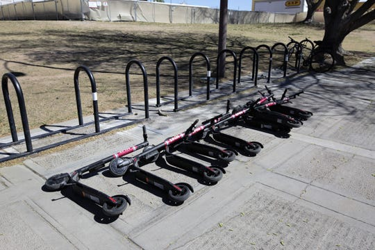 During spring break, Spin battery-operated kick scooters lay fallen near the the Corbett Student Union Center on New Mexico State University's main campus, March 29, 2019.