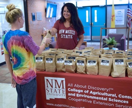 """Laura Bittner, New Mexico State University Extension family and consumer sciences agent in Valencia County, hands a Nutrition On Weekend snack pack to a Los Lunas Schools' Century High School student. A community collaboration is providing """"snack packs"""" for 177 students each week to help with their food insecurity situation."""