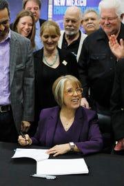 New Mexico Gov. Michelle Lujan Grisham, center, prepares to sign Senate Bill 2 in a ceremony at Albuquerque Studios on March 29, 2019.