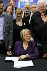 New Mexico Gov. Michelle Lujan Grisham, center, prepares to sign Senate Bill 2 in a ceremony at Albuquerque Studios on March 29, 2019.