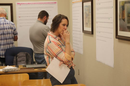 Jeri Strong, Eddy County public information officer and oil and gas liaison, looks over goals and objectives for future growth of the City of Carlsbad March 28 during a public meeting.
