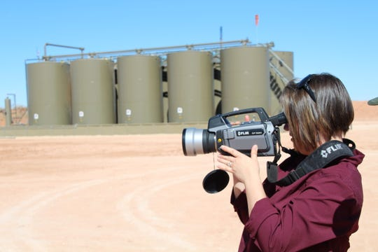 New Mexico State Land Commissioner Stephanie Garcia Richard looks for gas leaks at an oil and gas facility in Eddy County.
