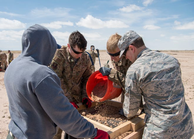 Airmen and a police officer from Doña Ana's bomb squad sift through dirt to find explosive debris, March 21, on Holloman Air Force Base, N.M. The group participated in a post-blast course provided by the Bureau of Alcohol, Tobacco, Firearms and Explosives' National Center for Explosives Training and Research.
